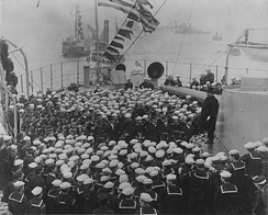 President Theodore Roosevelt (on the 12-inch (30 cm) gun turret at right) addresses officers and crewmen on Connecticut, in Hampton Roads, Virginia, upon her return from the Fleet's cruise around the world, 22 February 1909.