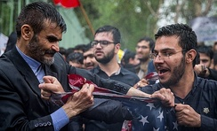 Two protesters in Iran tearing a U.S. flag at an anti-American rally after the United States withdrawal from the Joint Comprehensive Plan of Action