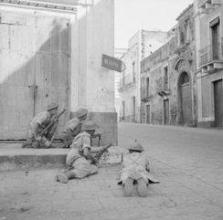Men of the 9th Battalion, Durham Light Infantry take cover on a street corner in Acireale, Sicily, 8 August 1943.