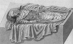 An open tomb seen from the side in a 45-degree angle from the ground. The corpse, with his head to the left, is dressed in fine funeral attire, wears a coronet and holds a sceptre in each hand.