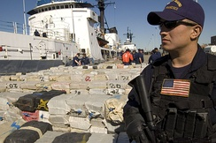 A Coast Guardmen stands guard over more than 40,000 pounds of cocaine worth an estimated $500 million being offloaded from the Cutter Sherman, April 23, 2007. The drugs were seized in three separate busts near Central America. The offload included approximately 38,000 pounds of cocaine seized in the largest cocaine bust in maritime history.
