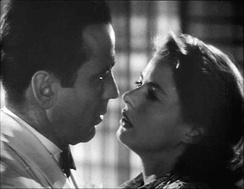 A black-and-white screenshot of a man and woman close together appearing ready to kiss.