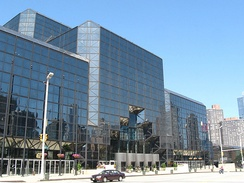 A building of dark tinted glass stands over a city street. The corners of the building are smoothed at 45-degree angles.
