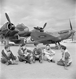 Five Malta-based RAF pilots sitting in front of a Beaufighter and a Spitfire at RAF Luqa, January 1943