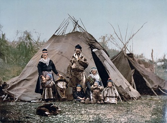 A Sami family in front of a goahti in the foreground and a lavvu in the background (the picture is taken around 1900).
