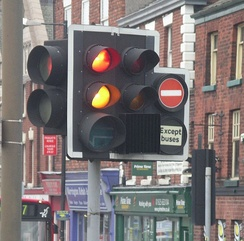 Traffic lights can have several additional lights for filter turns or bus lanes. This one designed by David Mellor introduced in 1965 and is used across the United Kingdom, Crown Dependencies and British Overseas Territories, which also shows the red + orange combination seen in a number of European countries, and a backing board with white border to increase the target value of the signal head. Improved visibility of the signal head is achieved during the night by using the retro-reflective white border.