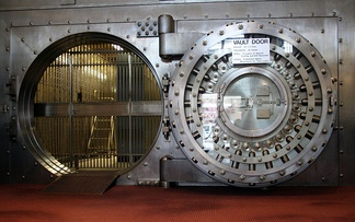This large 24-bolt Diebold vault door at the Winona National Bank was built in the early 1900s. On the right is the back side of the open door. To the right of the door's center are two linked boxes for the combination mechanisms and to the left is a four-movement time lock. This door has a four-point system for pressing the door into its opening (note the two stanchions left of the door opening) capable of exerting one third of the door's weight in closing force. Since this door weighs 22.5 short tons (20.4 t) this system is capable of applying 7.5 short tons-force (67 kN) inward.
