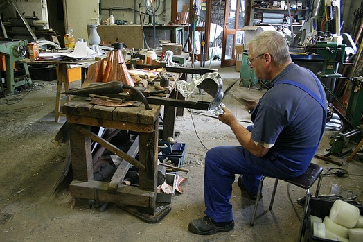 Dinandier (Coppersmith) at work in the last workshop of brassware subsisting in Dinant (Belgium).