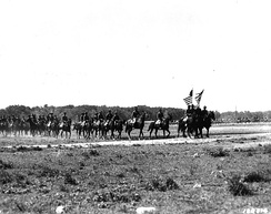 With colors flying and guidons down, the lead troops of the famous 9th Cavalry pass in review at the regiment's new home in rebuilt Camp Funston, Ft. Riley, Kansas, May 1941.