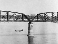 An RAF Hawker Hurricane Mk IIC flies alongside Aya Bridge, which spans the Irrawaddy River near Mandalay, Burma, during a low-level reconnaissance sortie, March 1945.
