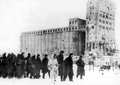 German soldiers as prisoners of war. In the background is the heavily fought-over Stalingrad grain elevator.