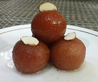 Gulab jamun topped with almond slivers is one of the most popular sweets from the Indian subcontinent.