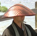 A Buddhist monk wearing a takuhatsugasa (also an ajirogasa).