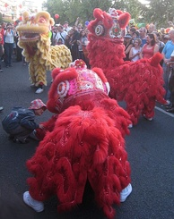 Lion dancers wearing bright red and yellow costumes