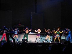 A long line of people in colorful clothes striking a pose on a stage with both their hands pointed up but their palms straight and looking to the right. Middle of them is a blond woman who sings into a microphone in her left hand.