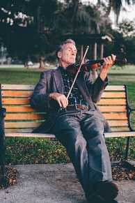 Man playing violin on a park bench.