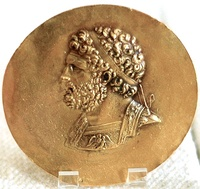 Left, a Niketerion (victory medallion) bearing the effigy of king Philip II of Macedon, 3rd century AD, probably minted during the reign of Roman Emperor Alexander Severus. Right, the ruins of the Philippeion at Olympia, Greece, which was built by Philip II of Macedon to celebrate his victory at the Battle of Chaeronea in 338 BC.[79]