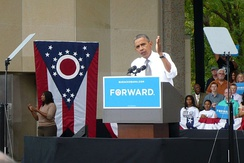 "A black man in a white shirt speaking on stage behind a podium with the word ""forward"" and in front of a red, white, and blue Ohio state flag."