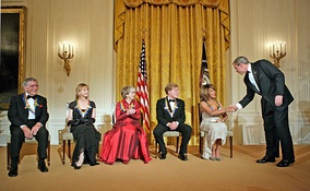 U.S. President George W. Bush congratulates Tina Turner during a reception for the Kennedy Center Honors in the East Room of the White House on December 4, 2005. From left, the other honorees are singer Tony Bennett, dancer Suzanne Farrell, actress Julie Harris, and actor Robert Redford.