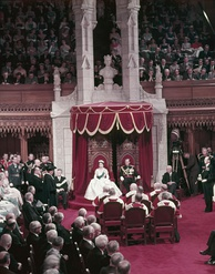 Queen Elizabeth II wearing her coronation gown, with Prince Philip during the opening of the 23rd Canadian Parliament, October 1957.
