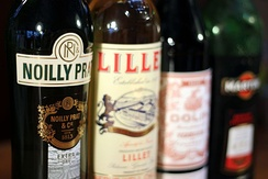 A collection of vermouth and quinquina bottles, including Noilly Prat Extra Dry, Lillet Blanc, Dolin Rouge, and Martini & Rossi Rosso