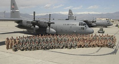 Deployed U.S. Air Force members of the 123rd Airlift Wing, Kentucky Air National Guard, pose with their Lockheed C-130H Hercules aircraft (s/n 91-1232, 91-1233) on a flightline in Afghanistan, 22 April 2009.