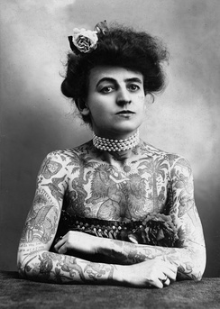 Mrs. M. Stevens Wagner with arms and chest covered in tattoos, 1907