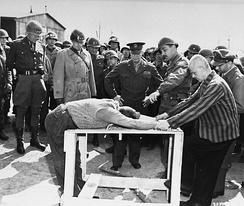 Survivors of the Ohrdruf concentration camp demonstrate torture methods used in the camp