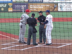 Umpires and managers prior to a New York–Penn League game in August 2017