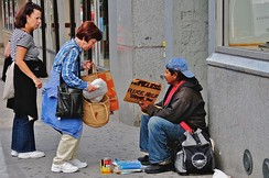 A woman giving a homeless man food in New York City, United States (2008)