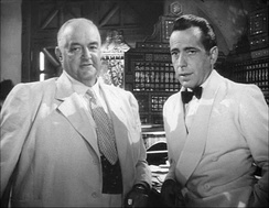 Bogart and Sydney Greenstreet, both wearing light-colored suits
