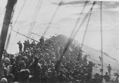 The crew of Zuikaku salute as the flag is lowered on the listing carrier after an airstrike. She was the last carrier participating in the attack on Pearl Harbor to be sunk.