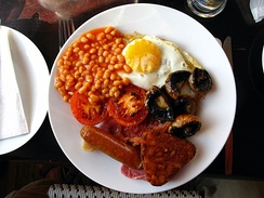 The full English breakfast often consists of bacon, fried egg, sausage, mushrooms, baked beans, toast, grilled tomatoes, and accompanied with tea or coffee.[7]