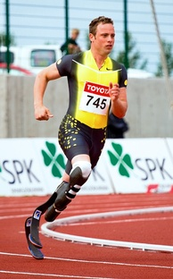 A man in a spandex singlet runs on a track. He has two prosthetics below the knees