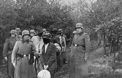Polish civilians wearing blindfolds photographed just before their execution by German soldiers in Palmiry forest, 1940