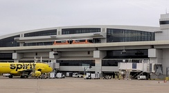 A Skylink train making a stop at Terminal E, next to a Spirit Airlines Airbus A320.