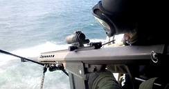 A U.S. Coast Guard TACLET marksman uses an M107 from a helicopter.