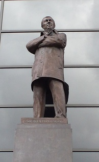 A bronze statue of a man wearing a coat with his arms folded.