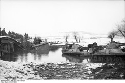 German forces with French-made H39 tanks fording a river.