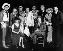 "Guest stars for the 1961 premiere episode of The Dick Powell Show, ""Who Killed Julie Greer?"".  Standing, from left: Ronald Reagan, Nick Adams, Lloyd Bridges, Mickey Rooney, Edgar Bergen, Jack Carson, Ralph Bellamy, Kay Thompson, Dean Jones. Seated, from left, Carolyn Jones and Dick Powell."