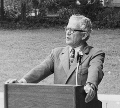 A man wearing a suit and glasses standing at a podium outside.