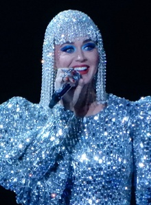 Katy Perry, a woman wearing a jeweled wig, smiling on stage wearing a jeweled outfit. She is holding a microphone to her mouth in her right hand.