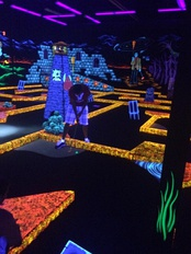 Golfer golfing at Monster Mini Golf, an indoor glow in the dark mini golf course
