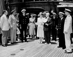 Marjorie Merriweather Post and her husband, Ambassador Joseph E. Davies, at center, with Carton Skinner at a presentation of a Naval Reserve Pennant.