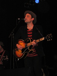 A man wearing a red and black-striped shirt, a black jacket, dark jeans and a hat; he is standing behind a microphone stand on a stage and playing a guitar
