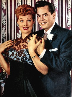 Colored glamorous shot of Lucille Ball and Arnaz standing. Both are smiling to the front. Ball at the left wears a ceremonial gown; Arnaz at right wears a tuxedo.