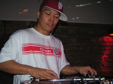 This photo of DJ Q-Bert shows the standard turntablist technique of manipulating the record with one hand while the other hand adjusts the controls on the DJ mixer.