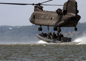 Special warfare combatant-craft crewmen attach a naval special warfare 11-meter rigid-hull inflatable boat to an Army Reserve CH-47 Chinook helicopter.