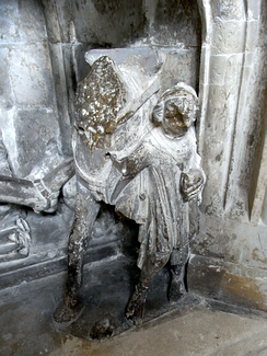 A squire holds the warhorse of his knight, detail from monument to Sir Richard Stapledon (d.1326), Exeter Cathedral.[1]