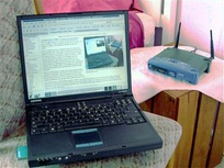 Laptop computer and typical home wireless router (right) connecting it to the Internet